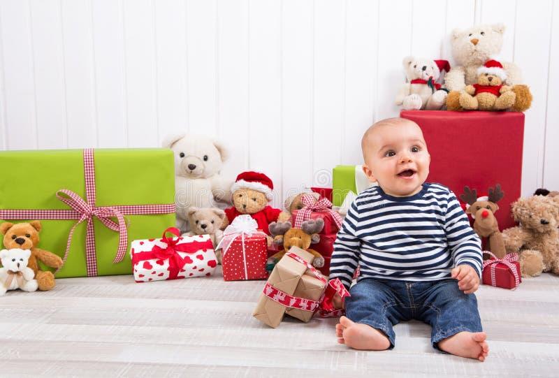 Noël et anniversaire - bébé mignon s'asseyant nu-pieds et regardant image stock