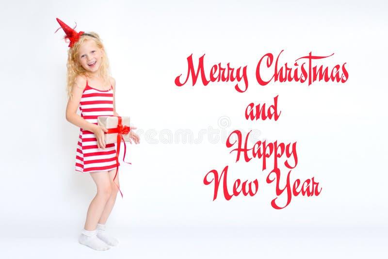 Noël et la nouvelle année cardent 2019 avec la petite fille blonde mignonne heureuse dans la robe rouge et blanche de costume de  images libres de droits