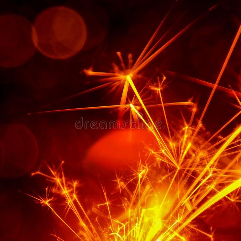 Noël et la nouvelle année font la fête le cierge magique avec le fond circulaire abstrait de bokeh image libre de droits