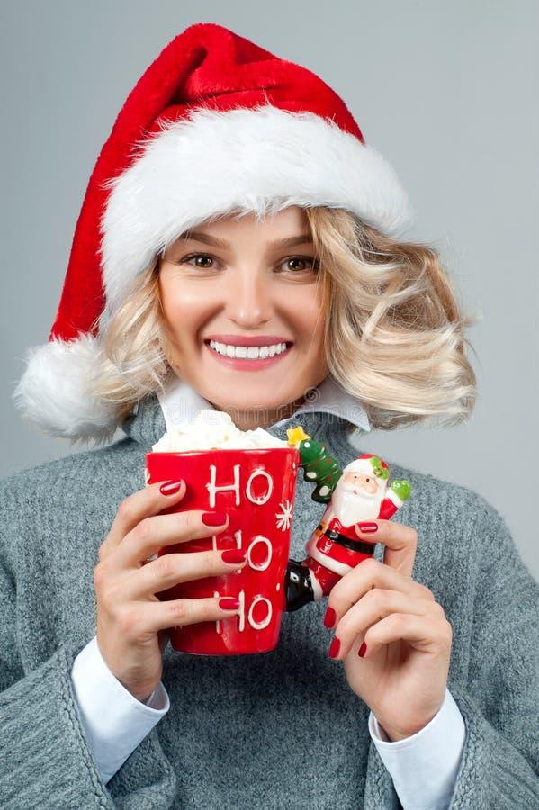 Noël et an neuf La femme dans le chapeau du ` s de Santa tient une tasse de café photos stock