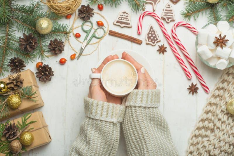 Noël, fond d'an neuf Plat-configuration, jouets éclatants, mains femelles avec la tasse du lat chaud, cannelle, ciseaux, au-dessu photos libres de droits