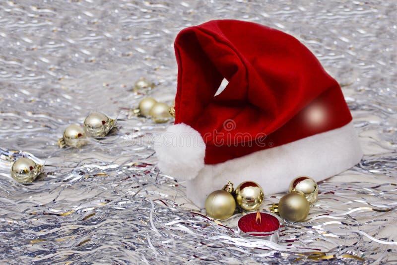 Noël joue les boules d'or, la bougie rouge brûlante, chapeau de Santa Claus image stock
