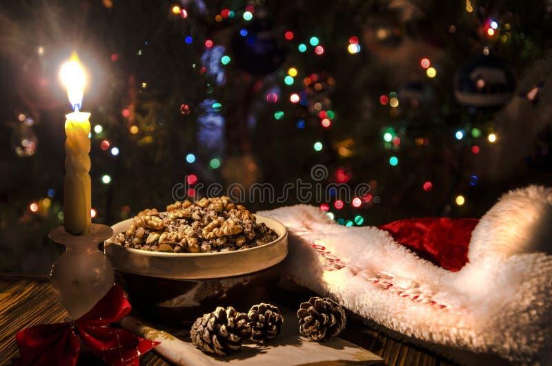 Noël, la soirée sur la table une cuvette avec des écrous, une bougie allumée, un chapeau de Santa Claus, images libres de droits