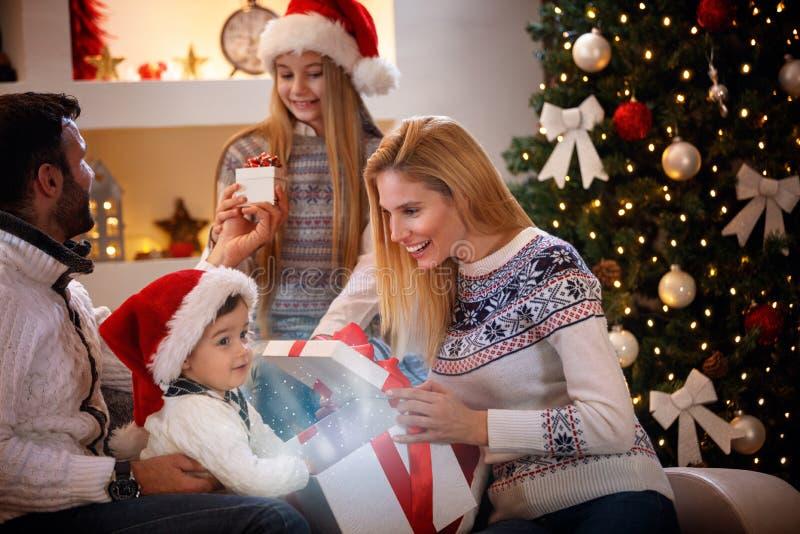 Noël magique - famille dans l'humeur de Noël échangeant des cadeaux photos libres de droits