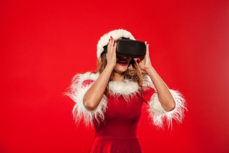 Noël, Noël, hiver, concept de bonheur - belle jeune brune avec de longs cheveux dans le port de chapeau d'aide de Santa photos libres de droits