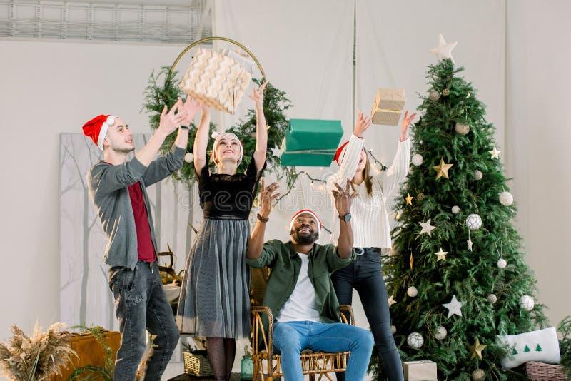 Noël, nouvelle année, vacances d'hiver Quatre amis célébrant Noël à la maison confortable, ayant l'amusement avec les boîtes actu photos stock