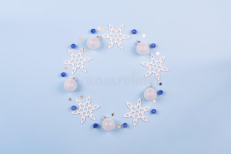 Noël ou composition en hiver Le flocon de neige, les baies bleues et les bals de décoration tressent sur le fond bleu en pastel N image stock