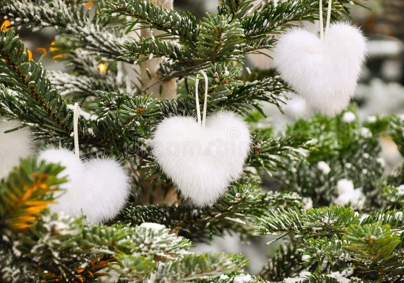 Noël pelucheux blanc de forme de coeur de décoration de Noël romantique créatif peu commun ou de nouvelle année joue sur le sapin image stock