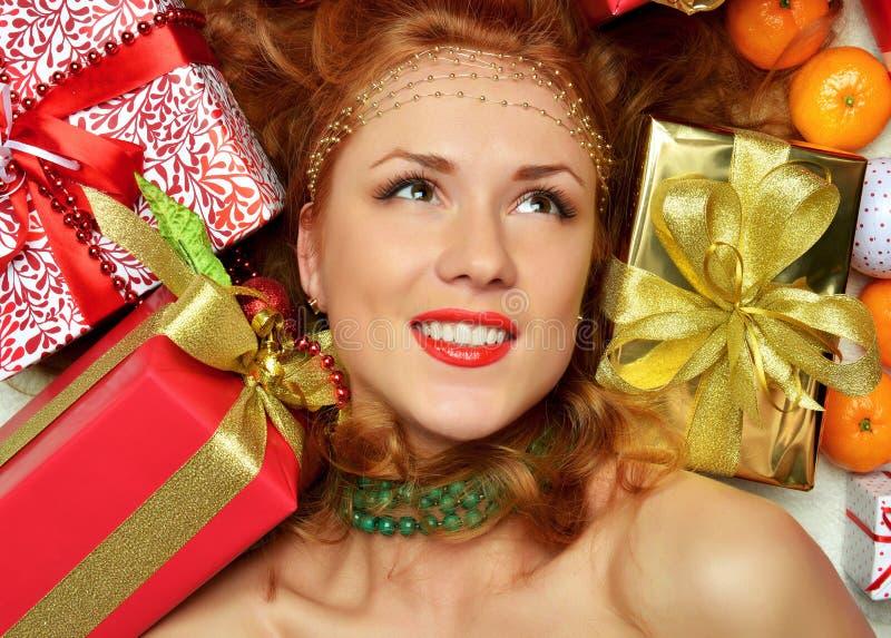 Noël rouge de prise heureuse de jeune femme a enveloppé le smilin actuel de cadeau images stock