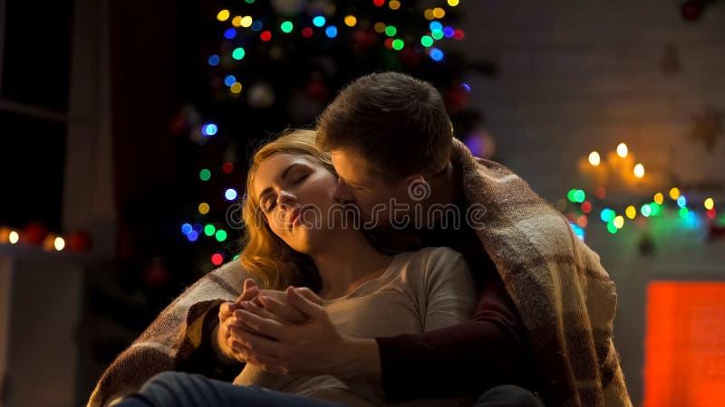 Noël tendre de dépense de couples ensemble, mains mettantes en forme de tasse de dames d'homme et baisers de elle photographie stock