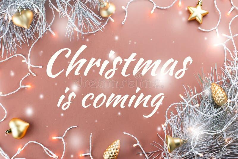 Noël vient - affiche ou carte postale avec des lumières de Noël, les ornements d'or, branches de sapin sur le fond brun chaud photo libre de droits