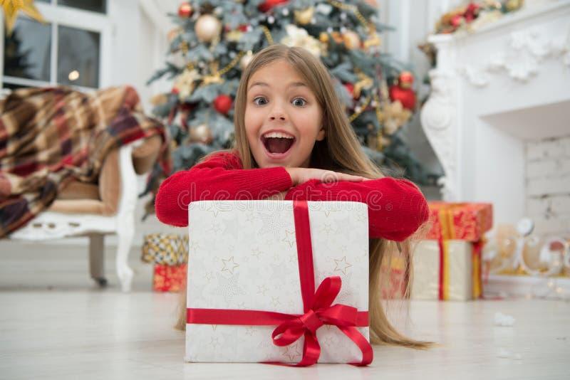 Noël vient La petite fille mignonne a reçu le cadeau Les meilleurs cadeaux de Noël Petite fille d'enfant dans la robe élégante et photos stock