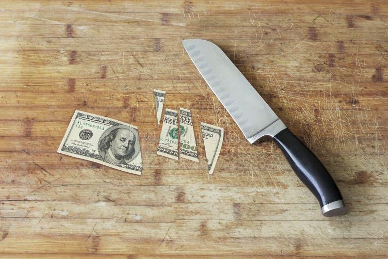 Nożowa tnąca deska i cięcie w sto dolarowych rachunków zdjęcia royalty free