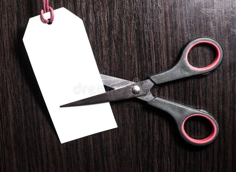 Nożyce ciąca papierowa biała metka na brown drewnianym tle zapas rabaty korzyść mapy pojęcia rysunkowy żeński ręki marketingu ekr obraz stock
