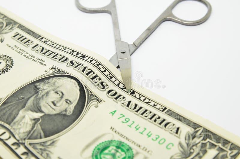 Nożyce ciący przez dolarowego rachunku fotografia stock