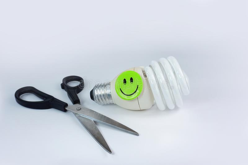 Nożyce energooszczędnej żarówki szczęśliwa smiley twarz odizolowywająca na białym tle zdjęcie stock