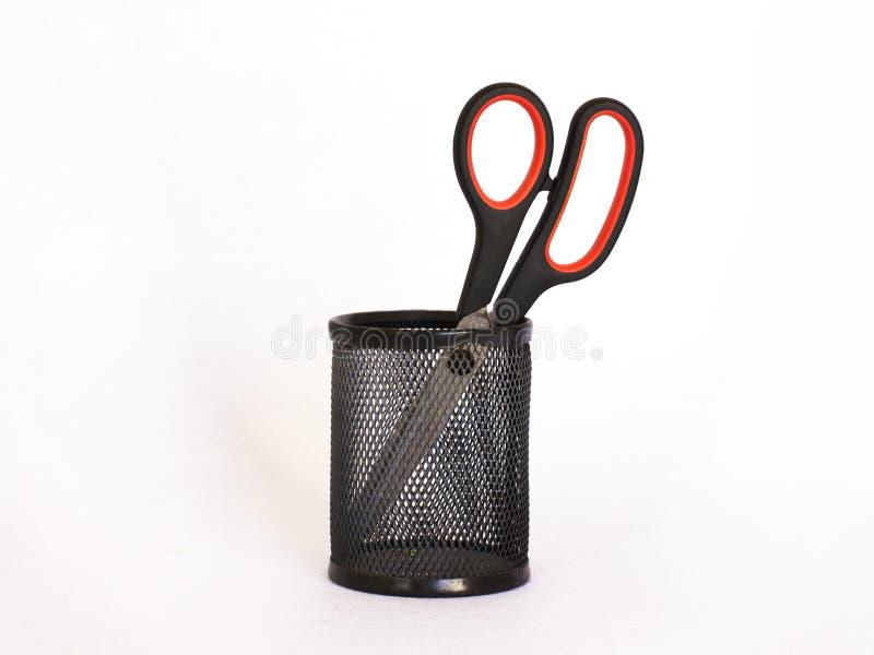 Nożyce z czerwoną rękojeścią w czarnym metalu właścicielu isolate obrazy stock