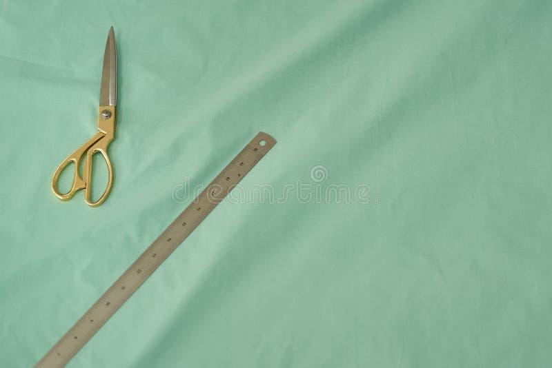 Nożyce z złocistymi rękojeściami kłamają na zielonym materiale obok żelaznej władcy fotografia royalty free
