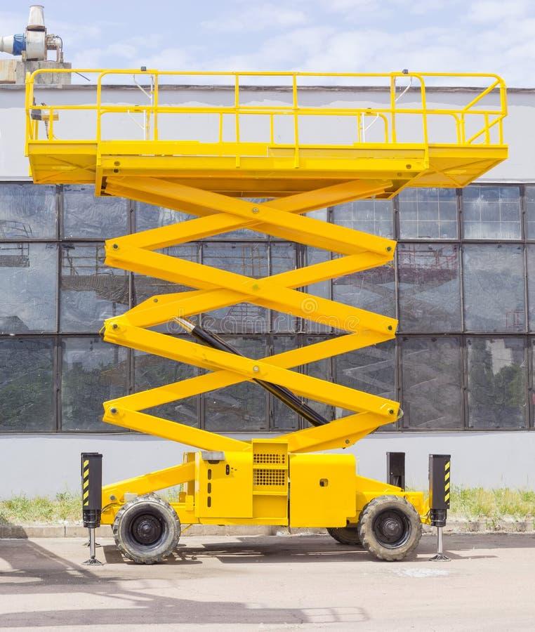 Nożycowy kołowy dźwignięcie przeciw przemysłowemu budynkowi fotografia stock