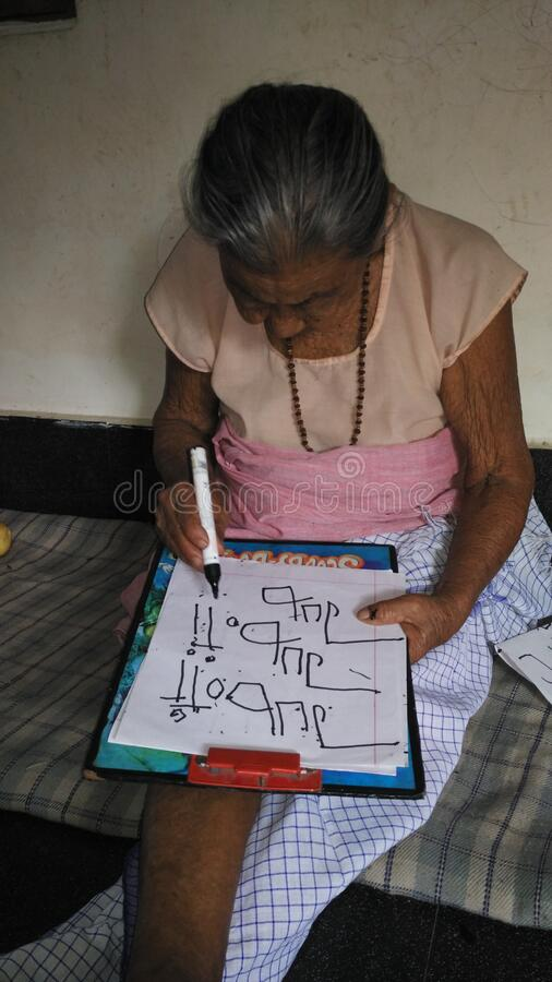 No age for learning. An old women trying so hard to write her own name. She is in her mid 80`s stock photography