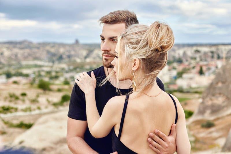 No amor o par oriental nas montanhas de Cappadocia abraça e beijos Amor e emoções que amam os pares que vacationing em Turquia cl foto de stock