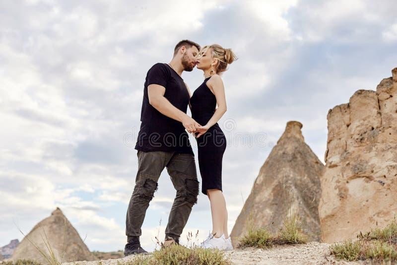 No amor o par oriental nas montanhas de Cappadocia abraça e beijos Amor e emoções que amam os pares que vacationing em Turquia cl fotografia de stock