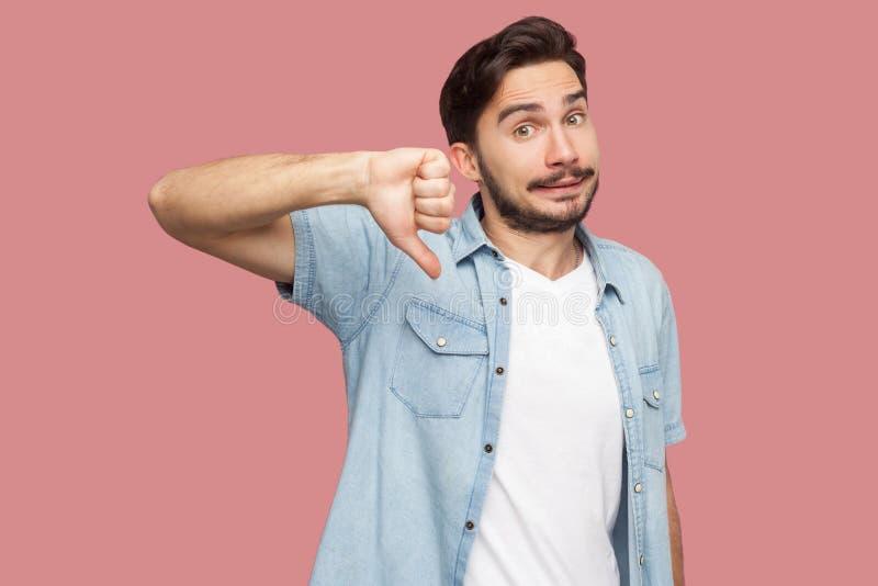 No, aversi?n Retrato del hombre joven barbudo hermoso descontento en la situaci?n azul de la camisa del estilo sport, pulgares ab foto de archivo