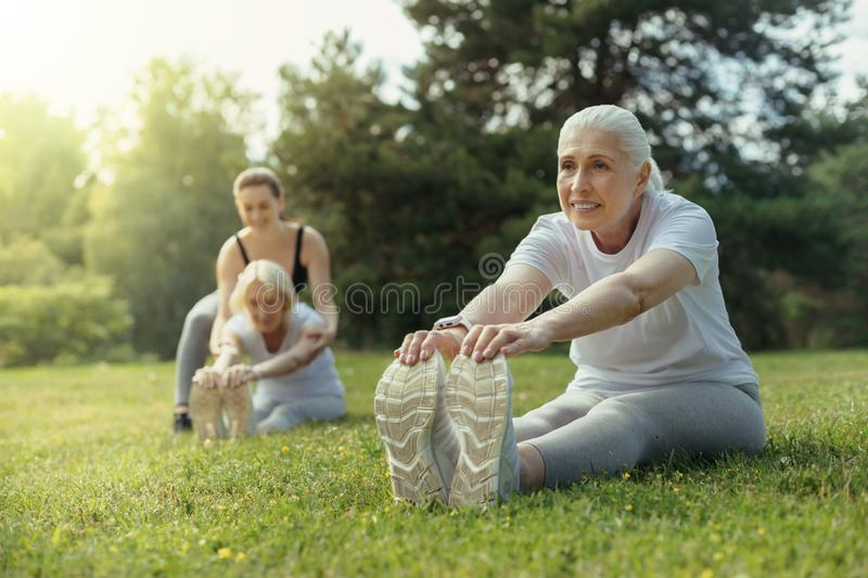 Positive minded elderly woman doing stretching exercise royalty free stock photo