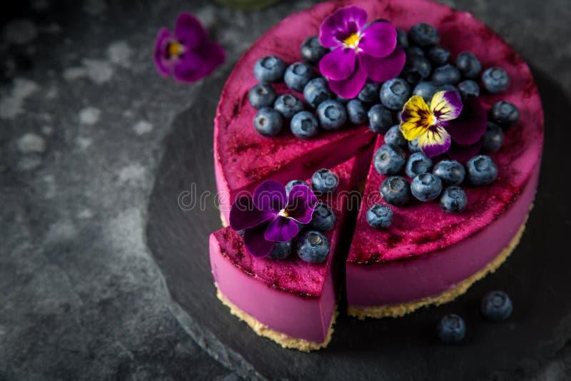 No baked blueberry mousse cake on dark background stock photography