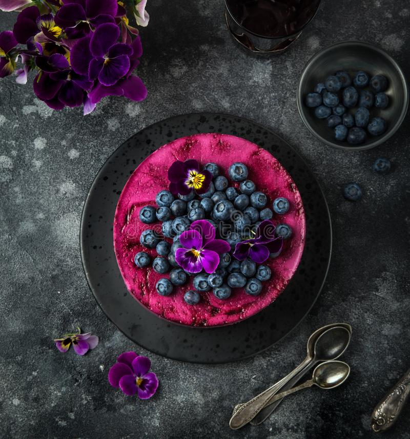 no baked blueberry mousse cake on dark background, selective focus, stock photos