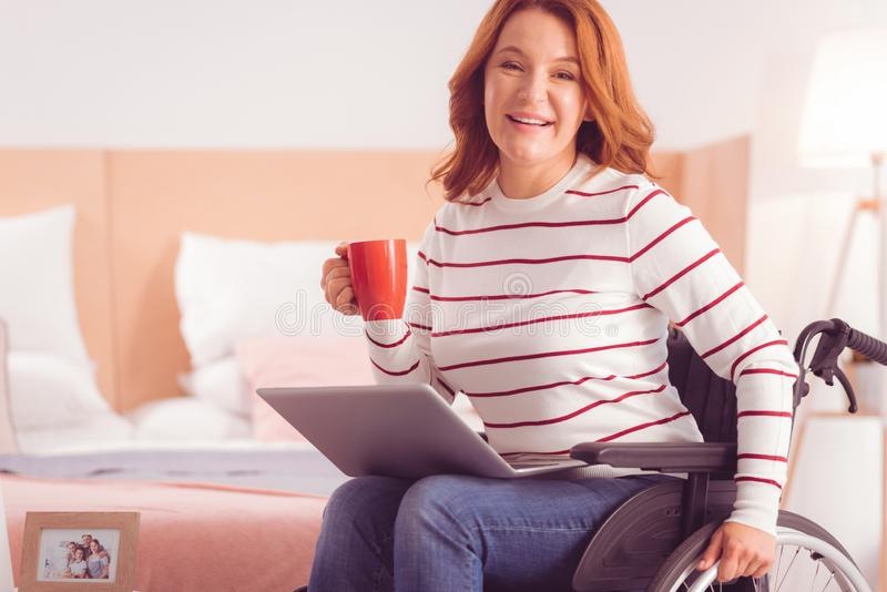 Happy immobile woman drinking tea royalty free stock photos
