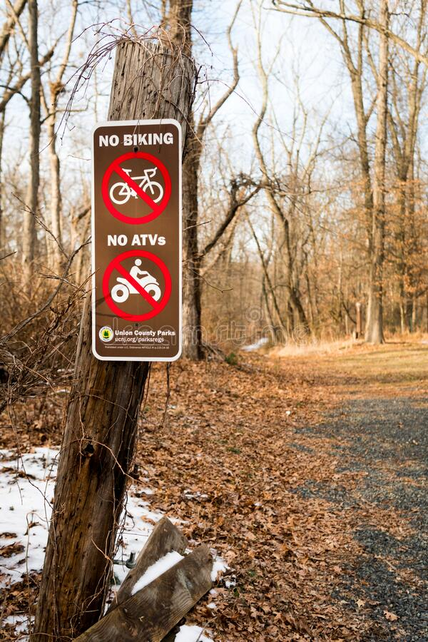 No biking, no ATVs sign at the entrance of Watchung Reservation. Union County Parks. Scotch Plains, New Jersey. Taken from Sky Top Dr street. Winter path royalty free stock photo