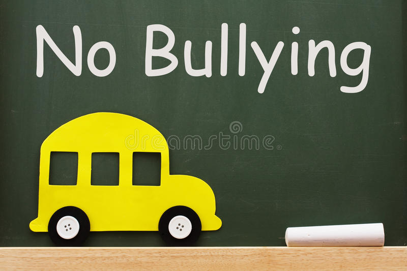 No bullying allowed. A school bus and chalk on a chalkboard with words no bullying, No bullying allowed stock image