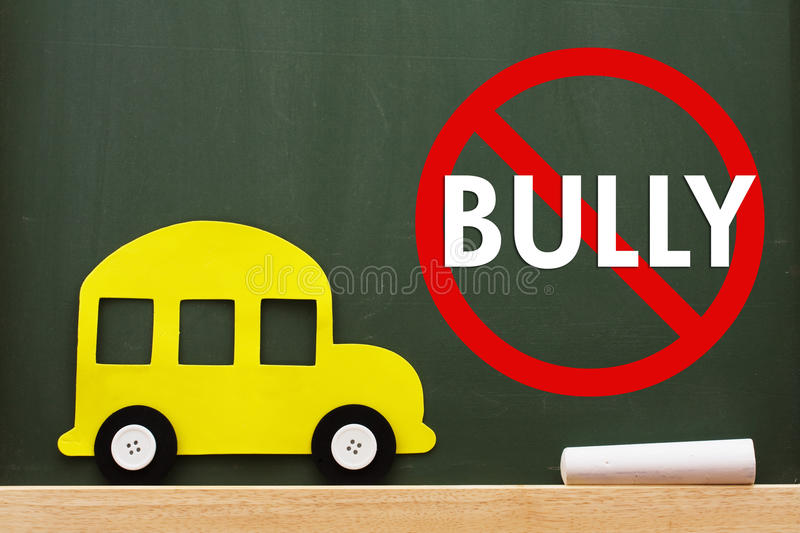 No bullying allowed. A school bus and chalk on a chalkboard with no bully sign, No bullying allowed stock photography