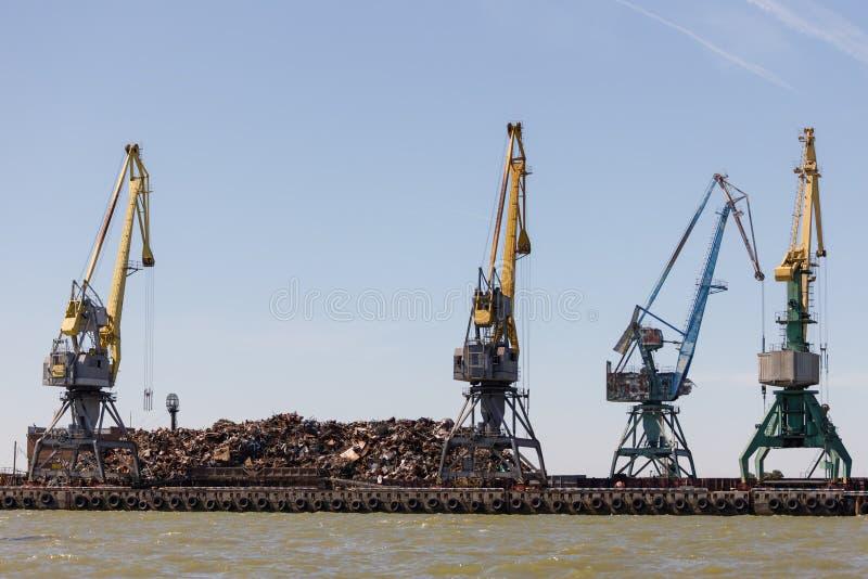 No cais encontra-se uma grande pilha da sucata de metal pretendida carregando na embarcação usando guindastes fotografia de stock royalty free
