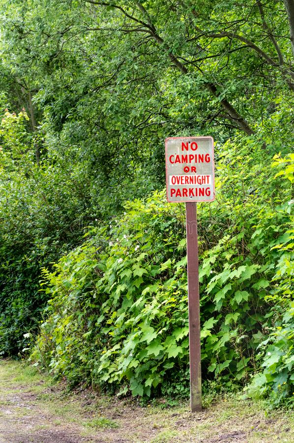 No camping or overnight parking sign, red lettering on rural road. royalty free stock image