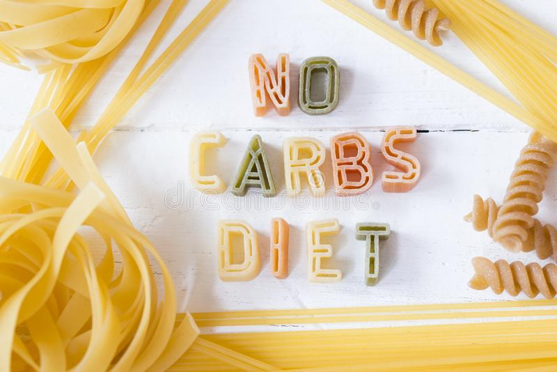 No carbs diet text written with colorful pastas on white wooden background royalty free stock image