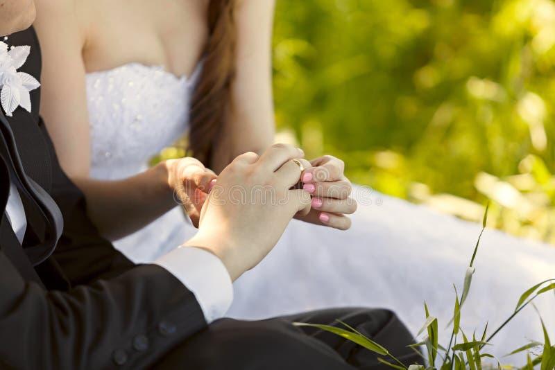 No casamento, a noiva que põe sobre o anel no dedo do noivo foto de stock