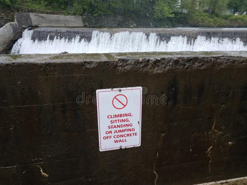 No climbing sitting or standing or jumping off wall sign and waterfall stock photography