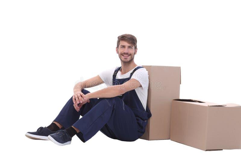 No crescimento completo homem de sorriso que senta-se perto das caixas de cartão fotografia de stock
