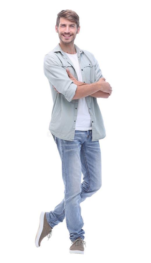 No crescimento completo homem novo de sorriso nas calças de brim imagem de stock