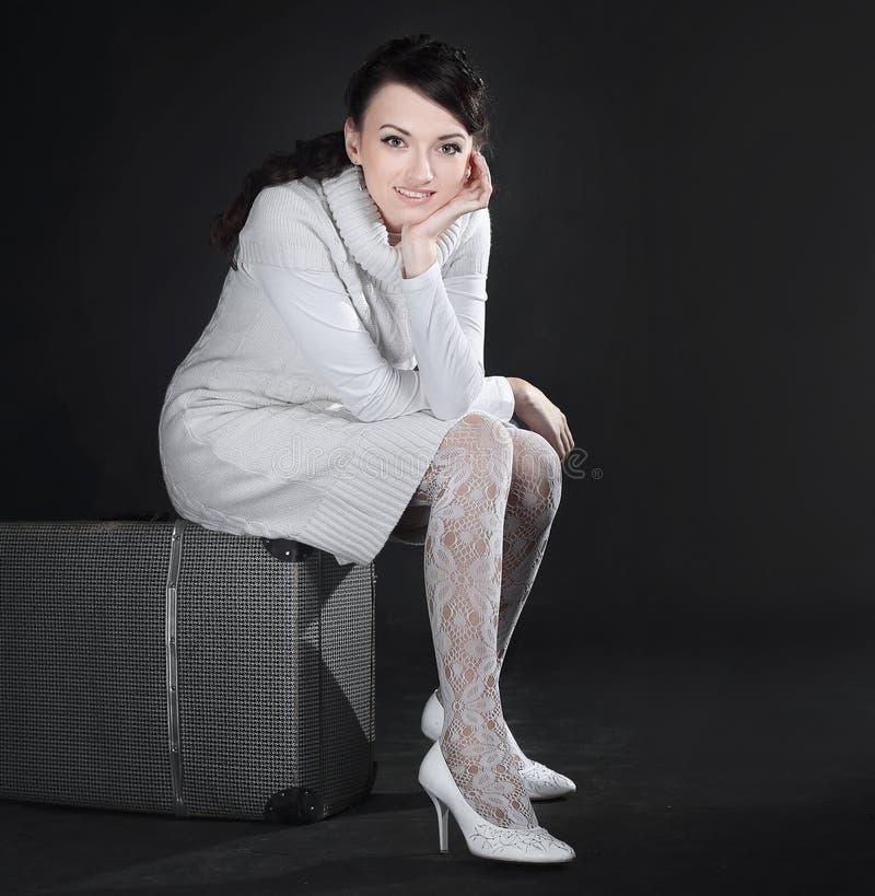 No crescimento completo jovem mulher de sorriso que senta-se em uma mala de viagem imagens de stock royalty free