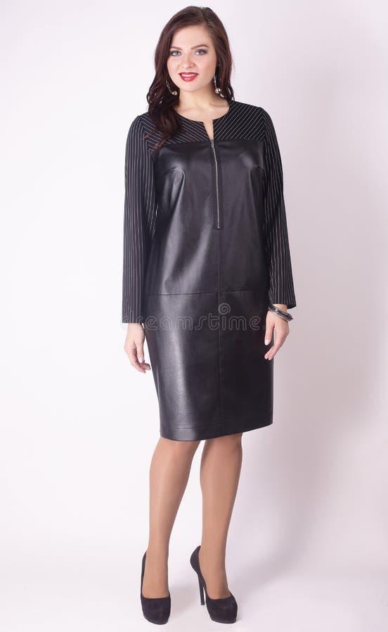 No crescimento completo modelo moderno da mulher em um vestido de couro preto Tamanho positivo fotografia de stock royalty free