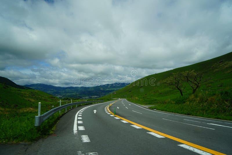 No dia nebuloso a viagem por estrada curvada após chover através da rota cênico da montanha verde local durante a primavera com s fotos de stock
