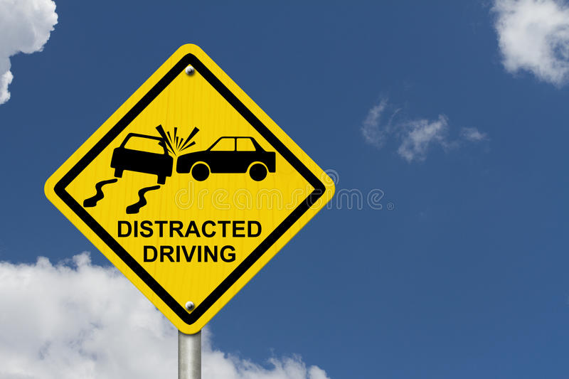 No Distracted Driving Sign. Yellow warning sign with words Distracted Driving and accident icon with sky background stock photo