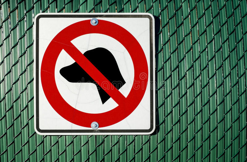 No dogs allowed sign. On a green metal fence royalty free stock photo