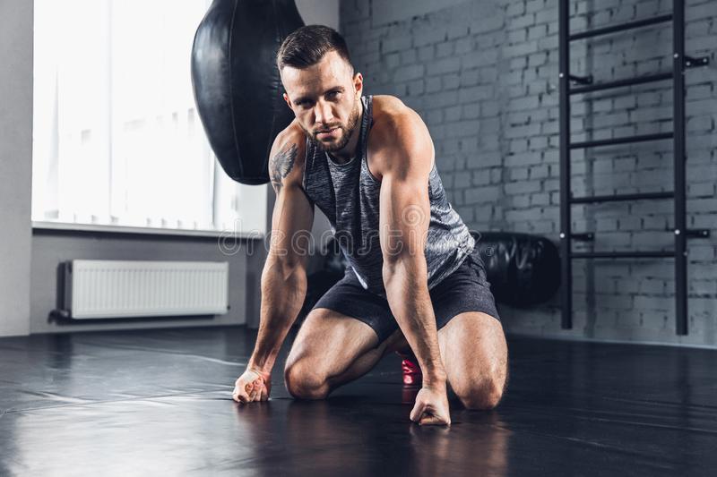 The athlete trains hard in the gym. Fitness and healthy life concept. No doubt. The athlete relaxing in the gym after strength exercises for different groups of royalty free stock image