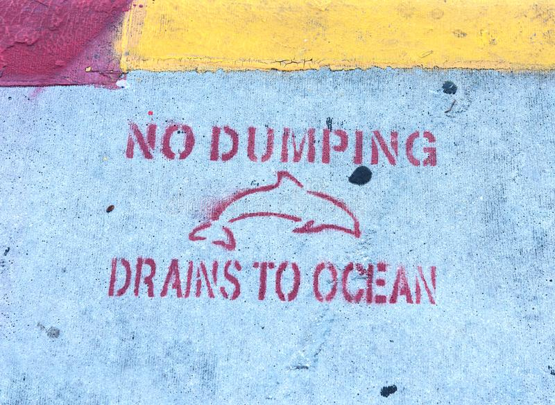 No Dumping Drains To Ocean writing on the sidewalk in Key West royalty free stock image