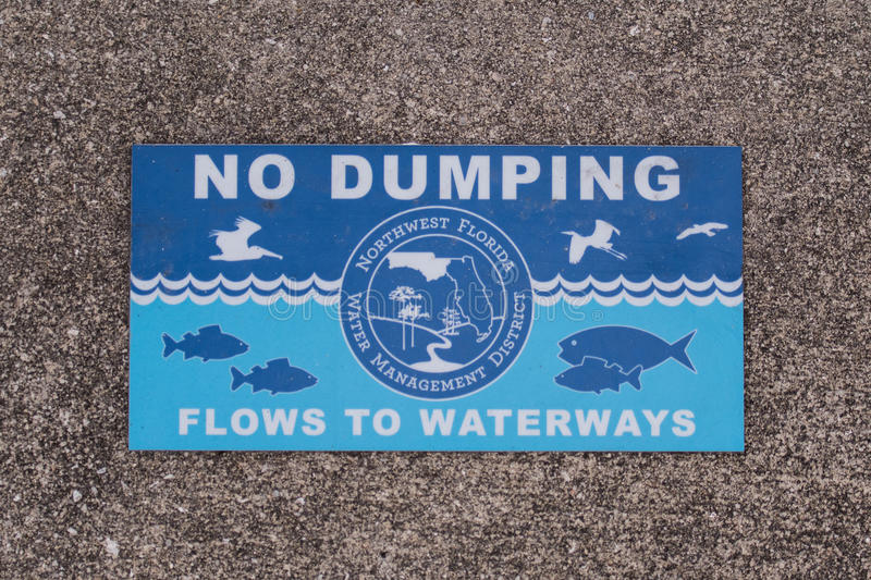 No Dumping Sign in Sidewalk. Reminds people to protect the local water royalty free stock images