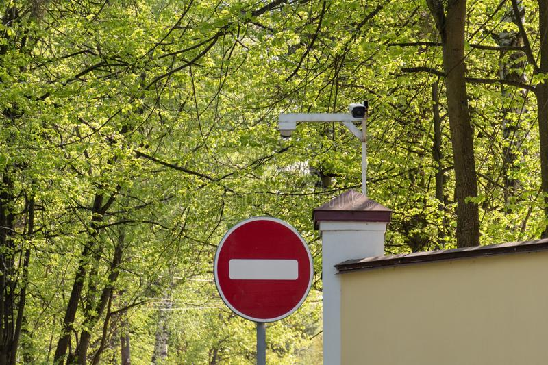 No entry Road sign and the security camera on the background of green trees royalty free stock images